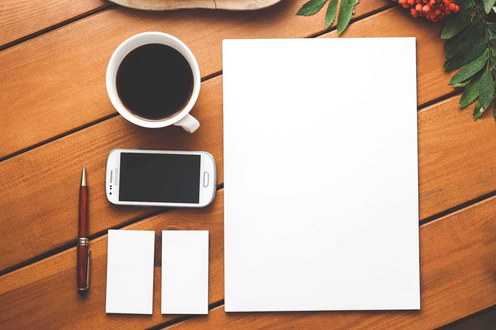 Picture of a desk with a coffee cup, pen and blank page of notes