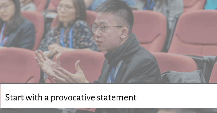 picture of a guy speaking with his hands up for starting your talk with a provacative statement