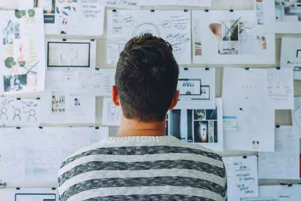 Man looking at whiteboard with too many options.